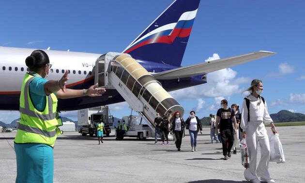 Hành khách rời chuyến bay từ Moskva tới đảo Male ở Seychelles hôm 2/4. Ảnh: AFP.