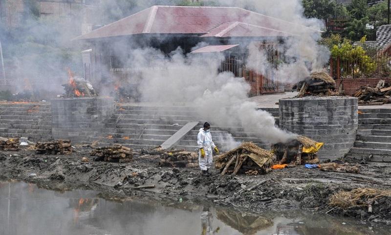 Người đàn ông mặc đồ bảo hộ đứng giữa đống lửa hỏa táng các nạn nhân chết vì Covid-19 trên bờ sông Bagmati ở Kathmandu, Nepal hôm 7/5. Ảnh: AFP.