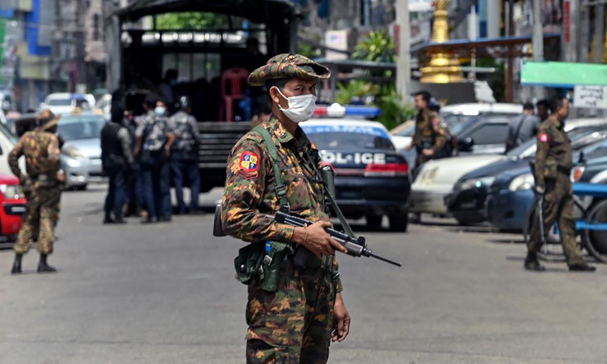 Binh sĩ và cảnh sát Myanmar đứng gác tại một chốt an ninh gần nơi diễn ra biểu tình ở Yangon ngày 7/5. Ảnh: AFP.
