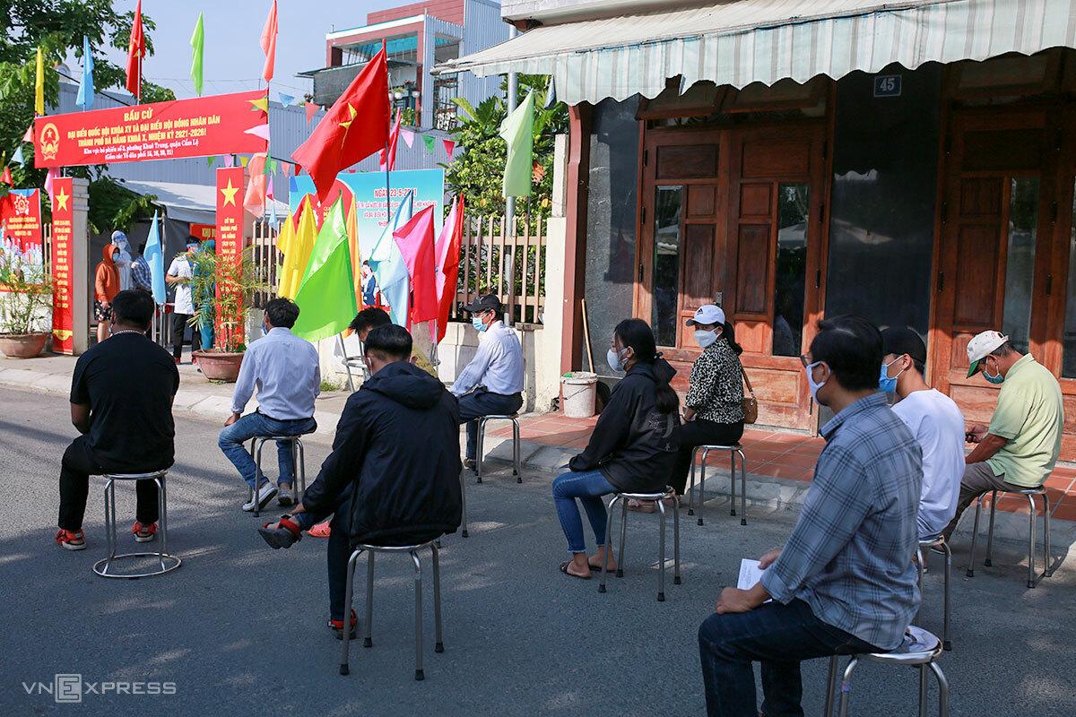 Người dân ngồi giãn cách trước khi vào khu vực bầu cử. Ảnh: Nguyễn Đông.