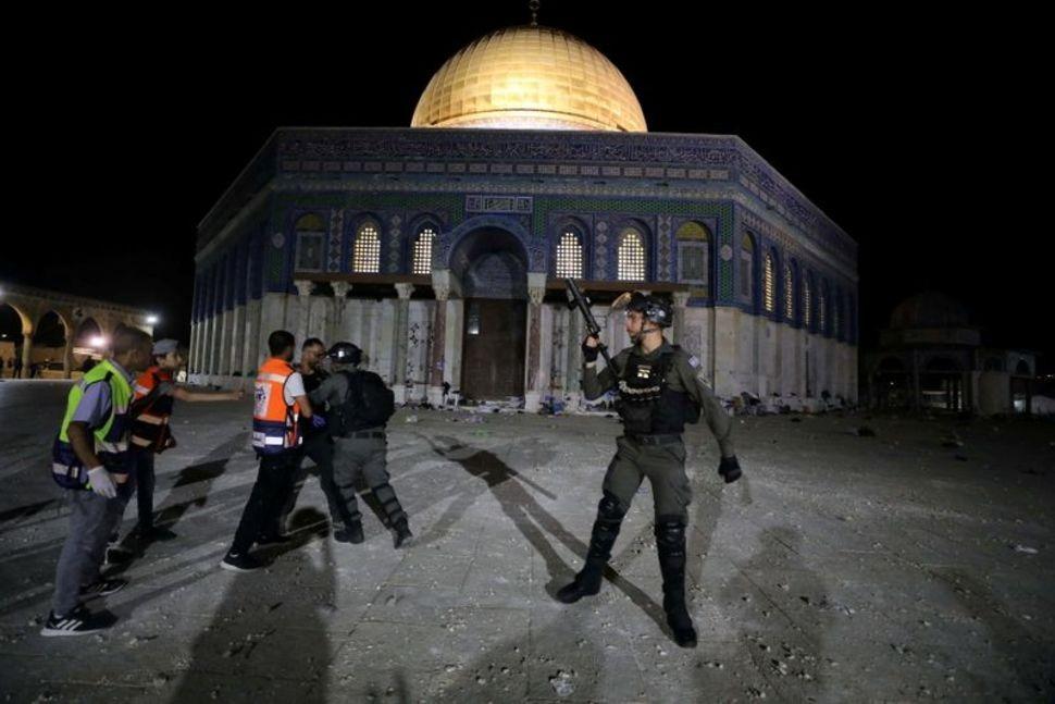 Cảnh sát Israel xô xát với một người Palestine trước Mái vòm Đá trong cuộc đụng độ tại Núi Đền, một ngọn đồi tại Thành cổ Jerusalem hôm 7/5. Ảnh: Reuters