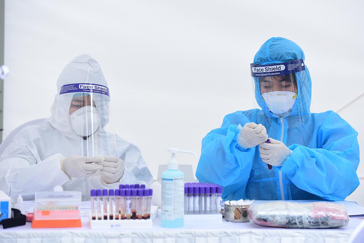 Nhân viên y tế làm việc ở một trạm xét nghiệm nhanh Covid-19 tại Hà Nội. Ảnh: Giang Huy.