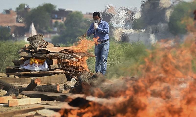 Một thành viên gia đình cầu nguyện trong lễ hỏa táng người thân chết vì Covid-19 tại khu hỏa táng ở thành phố Allahabad, bang Uttar Pradesh, Ấn Độ hôm 8/5. Ảnh: AFP.