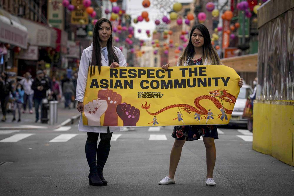 Michelle Lee (trái) và Ida Chen cầm biểu ngữ Tôn trọng cộng đồng gốc Á tại khu phố Tàu ở New York hồi tháng 4. Ảnh: AP.