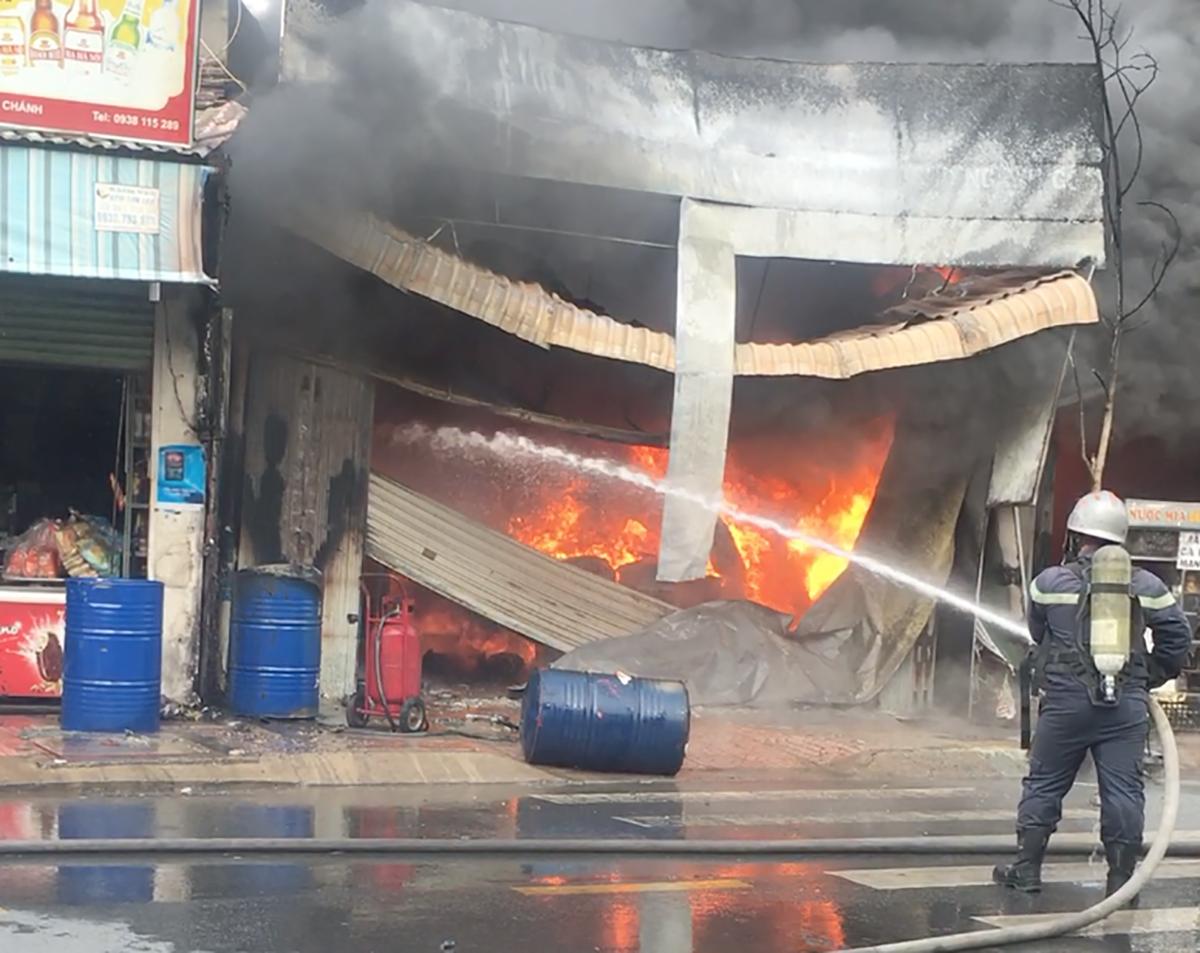 Lửa cháy ngùn ngụt tại cửa hàng sơn lan sang hai nhà dân. Ảnh: Thế Hùng.