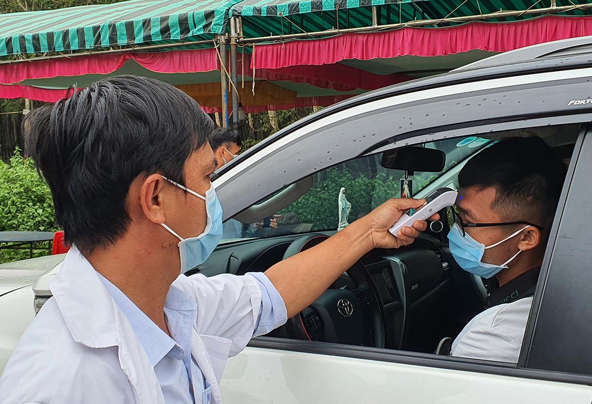 Nhân viên y tế đo thân nhiệt tài xế chạy ôtô trên quốc lộ 56 vào Bà Rịa - Vũng Tàu. Ảnh: Phong Vũ.