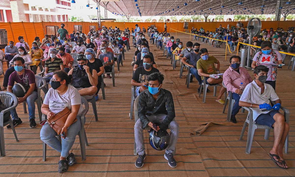 Người dân ngồi chờ tiêm vaccine Covid-19 tại một bệnh viện ở New Delhi tuần trước. Ảnh: AFP.