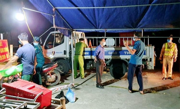 Lực lượng công an, dân phòng thu dọn đồ đạc tại một chốt kiểm soát ở thôn Việt Yên, tối 10/5. Ảnh: Thạch Hà