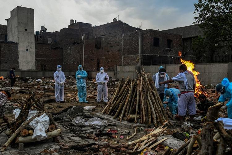 Thân nhân thực hiện các nghi thức cuối cùng trước khi đưa người quá cố lên giàn thiêu tại khu hỏa táng Seemapuri hôm 6/5. Ảnh: NYTimes.