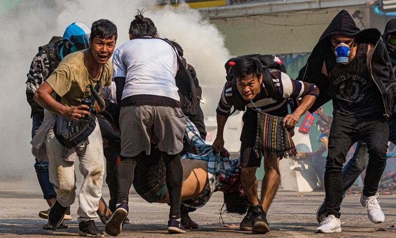 Người biểu tình khiêng một người đàn ông bị thương do đạn thật của lực lượng an ninh trong cuộc biểu tình ở Yangon, Myanmar ngày 17/3. Ảnh: AFP.