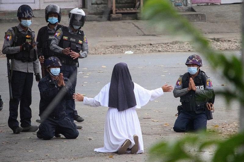 Nữ tu Ann Rose Nu Tawng quỳ trước cảnh sát ở thành phố Myitkyina, bang Kachin hồi tháng 3, trong khi hai cảnh sát cũng quỳ với bà. Ảnh: AFP.