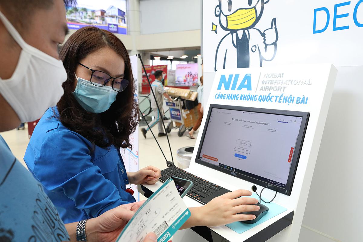 Nhân viên sân bay  hỗ trợ hành khách khai báo y tế trên máy tính. Ảnh: Ngọc Thành.