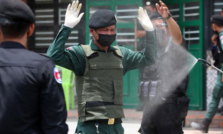 Một sĩ quan cảnh sát Campuchia được phun khử khuẩn. Ảnh: Khmer Times.