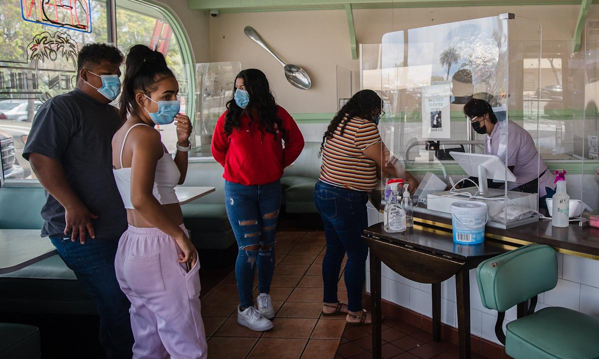 Khách hàng đeo khẩu trang đứng chờ thanh toán tại một quán cà phê ở San Diego, bang California cuối tháng 4. Ảnh: NYTimes.