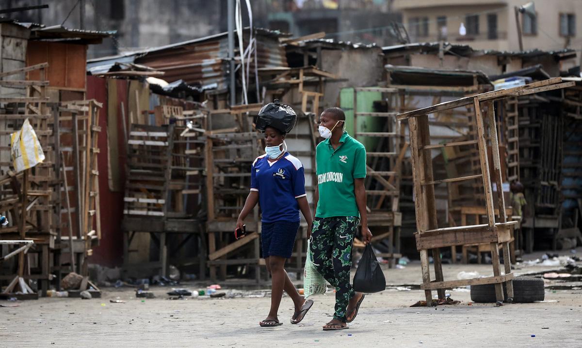 Hai người đi qua khu phố vắng tanh vì lệnh phong tỏa ngăn Covid-19 ở thủ đô Lagos, Nigeria hồi tháng 3/2020. Ảnh: AP.