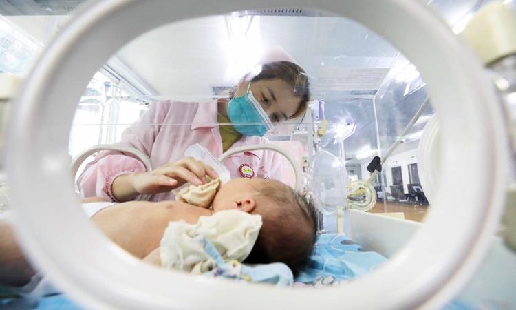 Y tá chăm sóc một em bé mới chào đời tại Bệnh viện Nhân dân Dung An thuộc huyện Dung An, Liễu Châu, khu tự trị dân tộc Choang, Quảng Tây, Trung Quốc, hồi tháng một. Ảnh: Xinhua.