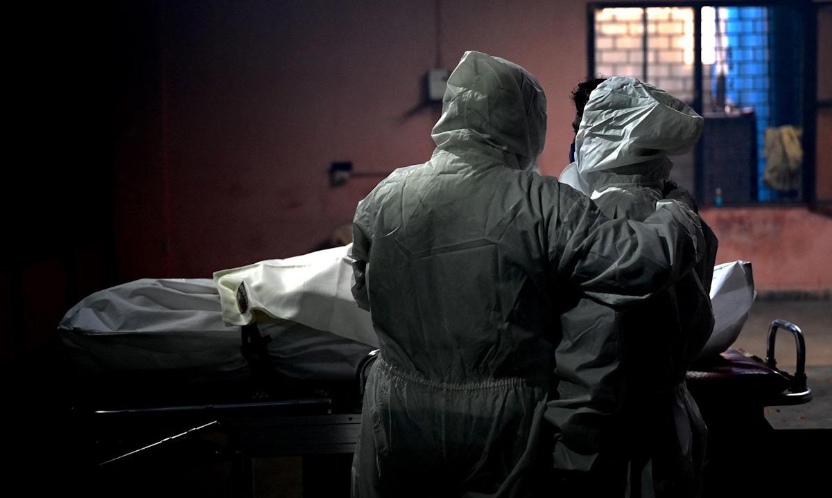 Người nhà đứng bên thi thể nạn nhân Covid-19 tại một nhà hỏa táng ở New Delhi ngày 11/5. Ảnh: AFP.