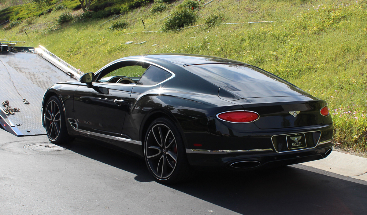 The Bentley model also purchased with the Covid-19 support money is being taken away by the police.  Photo: US Attorney LA