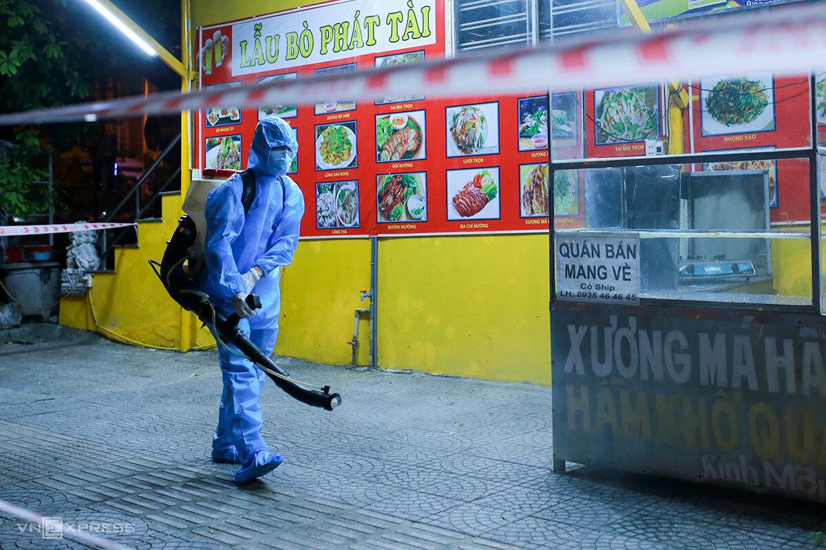 Nhân viên y tế phun khử khuẩn khu hàng quán, dân cư trước cổng Khu công nghiệp An Đồn. Ảnh: Nguyễn Đông.