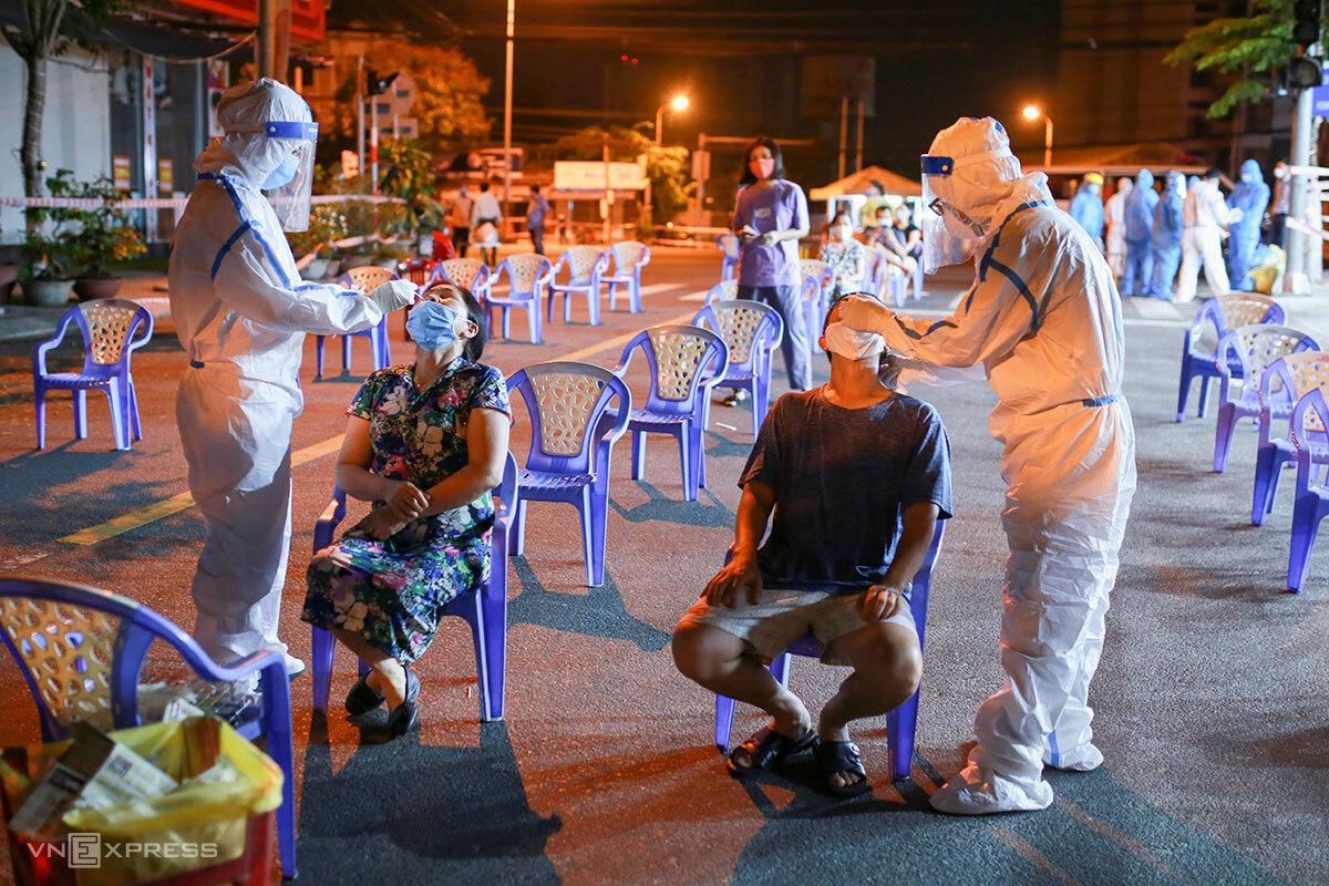 Nhân viên y tế lấy mẫu xét nghiệm cho người dân ngoài khu công nghiệp, khuya ngày 11/5. Ảnh: Nguyễn Đông.