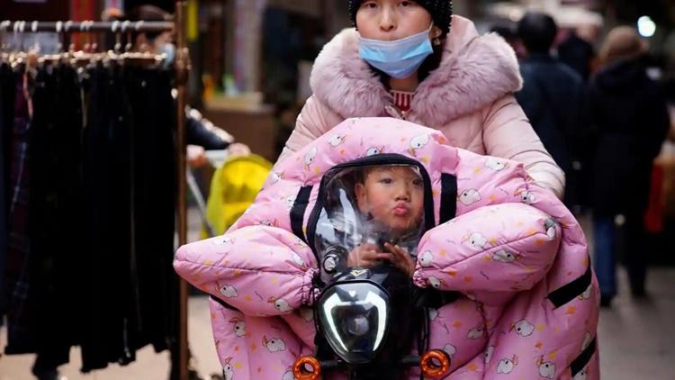 Người phụ nữ đeo khẩu trang chở con trên xe máy tại thành phố Vũ Hán, tỉnh Hồ Bắc, Trung Quốc, hồi năm ngoái.