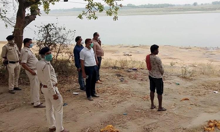 Cảnh sát giám sát việc chôn cất các thi thể trôi dạt vào bờ sông Hằng ở làng Chausa, huyện Buxar, bang Bihar hôm 11/5. Ảnh: PTI.