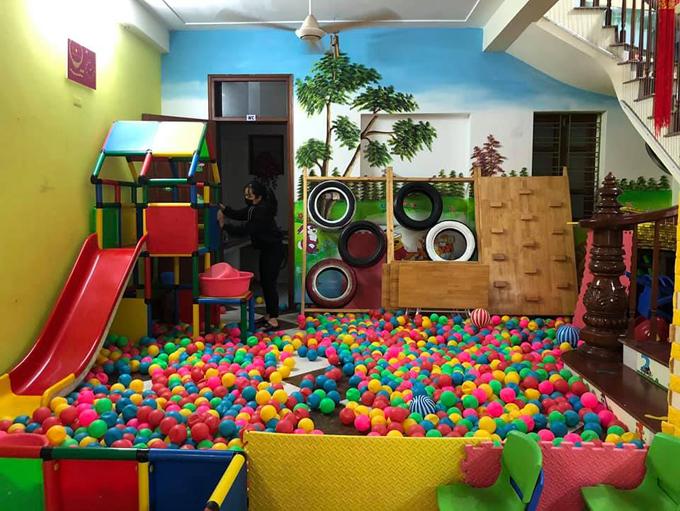 Giáo viên vệ sinh khu vực vui chơi ở một trường mầm non tư thục trước khi đón trẻ trở lại trường.