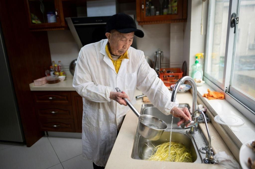 Yu Fuxi, 103 tuổi, nấu cơm trong nhà riêng tại thành phố Như Cao, tỉnh Giang Tô, hôm 31/3. Ảnh: AFP