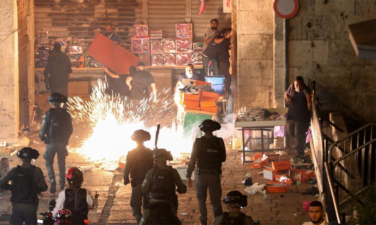 Người Palestine ném pháo hoa đáp trả sau khi lực lượng cảnh sát Israel bắn một quả lựu đạn gây choáng trong cuộc đụng độ tại Cổng Damascus ở Jerusalem ngày 9/5. Ảnh: Reuters.