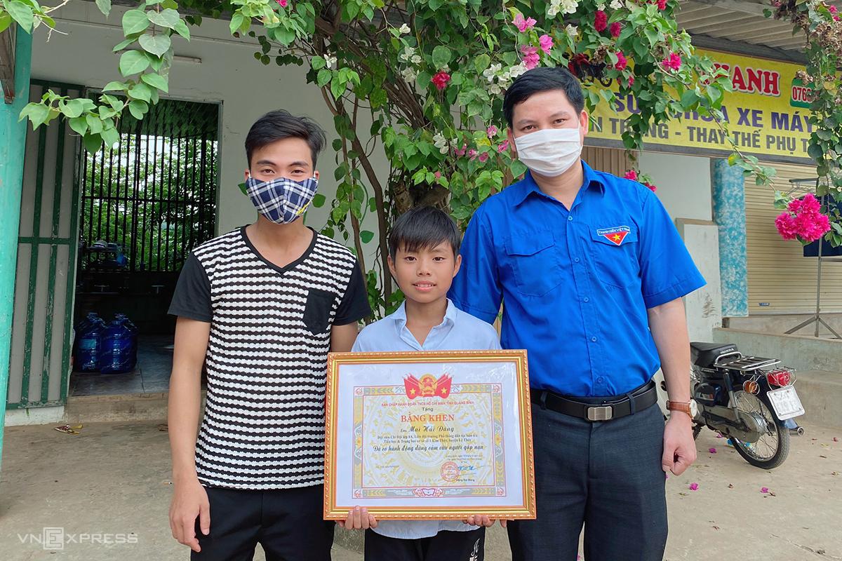 Nam sinh Mai Hải Đăng (giữa) nhận bằng khen của Tỉnh đoàn Quảng Bình vì hành động dũng cảm cứu người đuổi nước. Ảnh: Lệ Quyên