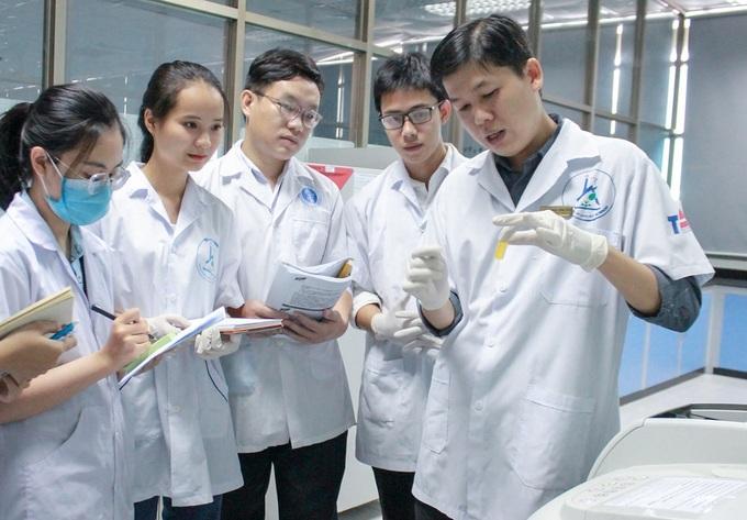 TS Chinh hướng dẫn sinh viên tách chiết hợp chất trong phòng thí nghiệm. Ảnh: NVCC.