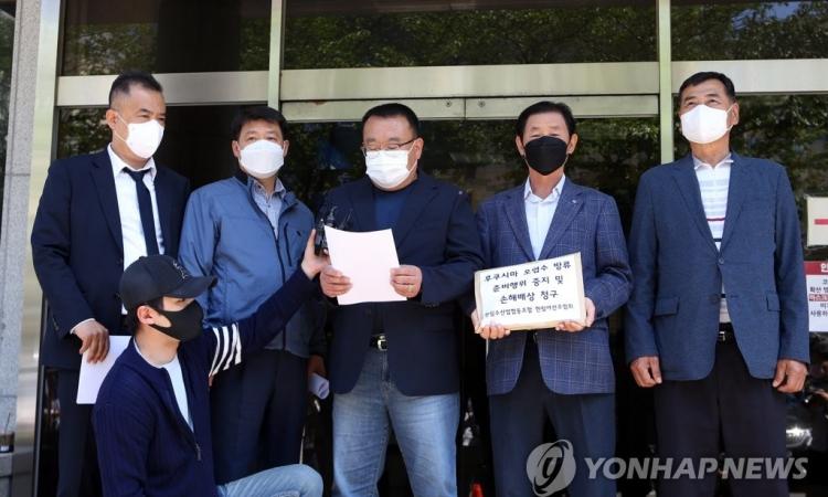 Các quan chức ngành thủy sản Jeju thông báo vụ kiện chính phủ Nhật Bản bên ngoài tòa án Jeju hôm nay. Ảnh: Yonhap.