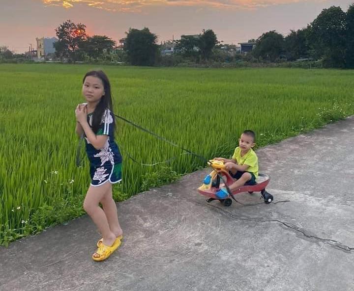 Em trai vui vẻ được chị kéo xe đi chơi.