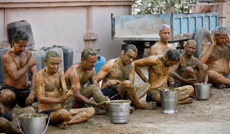 Các tín đồ ở ngoại ô thành phố Ahmedabad, Ấn Độ, bôi phân bò lên người với niềm tin chúng giúp đuổi Covid-19. Ảnh: Reuters.