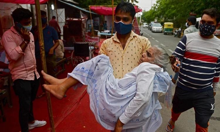 Bệnh nhân Covid-19 được người nhà bế tới một địa điểm cung cấp oxy miễn phí ở ngoại ô thủ đô New Delhi, Ấn Độ. Ảnh: AFP.