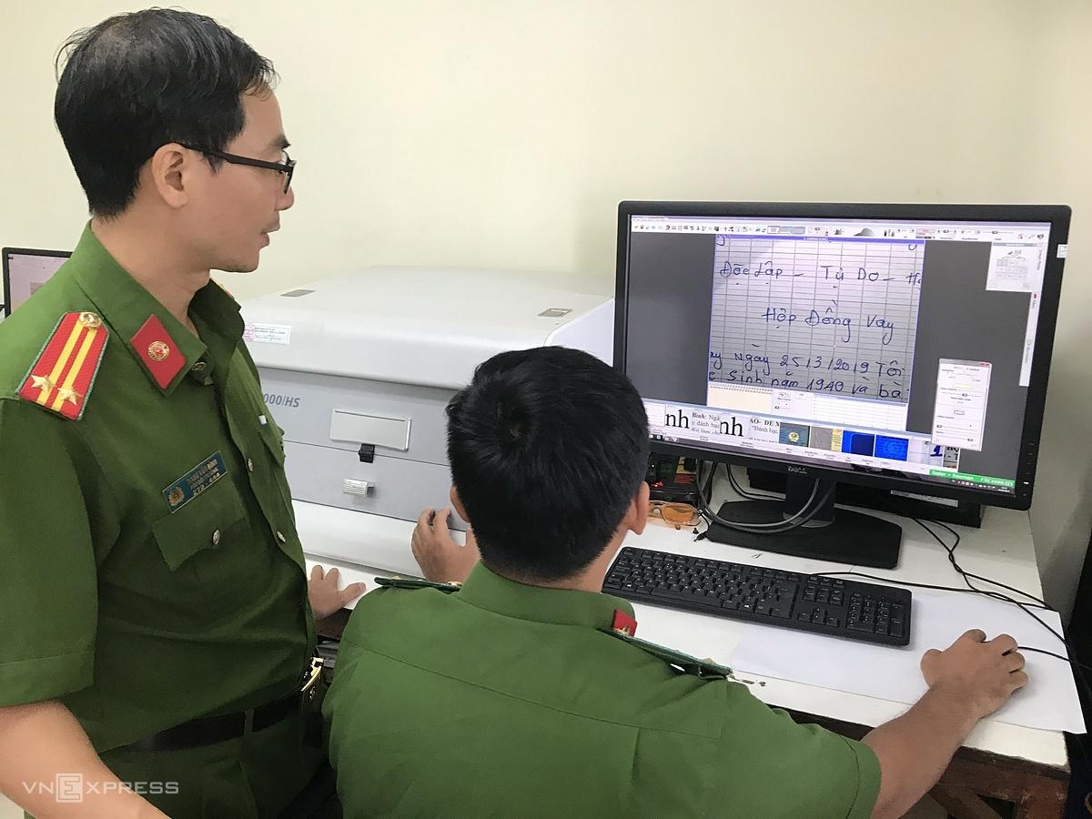 Trung tá Đặng Văn Bình (trái) trao đổi kinh nghiệm giám định với đồng đội. Ảnh: Việt Anh.