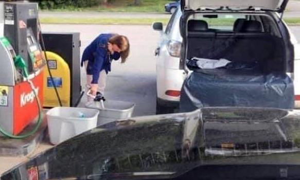 Một phụ nữ bơm xăng vào hai chiếc thùng nhựa, đựng vào cốp xe đã trải sẵn vải bạt. Ảnh: Rideyourbike