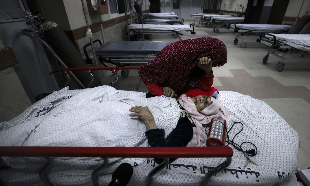Cô gái Palestine khóc bên người bà bị thương tại bệnh viện Al-Shifa, sau khi Israel không kích trại tị nạn Shati ở Dải Gaza rạng sáng nay. Ảnh: AFP.