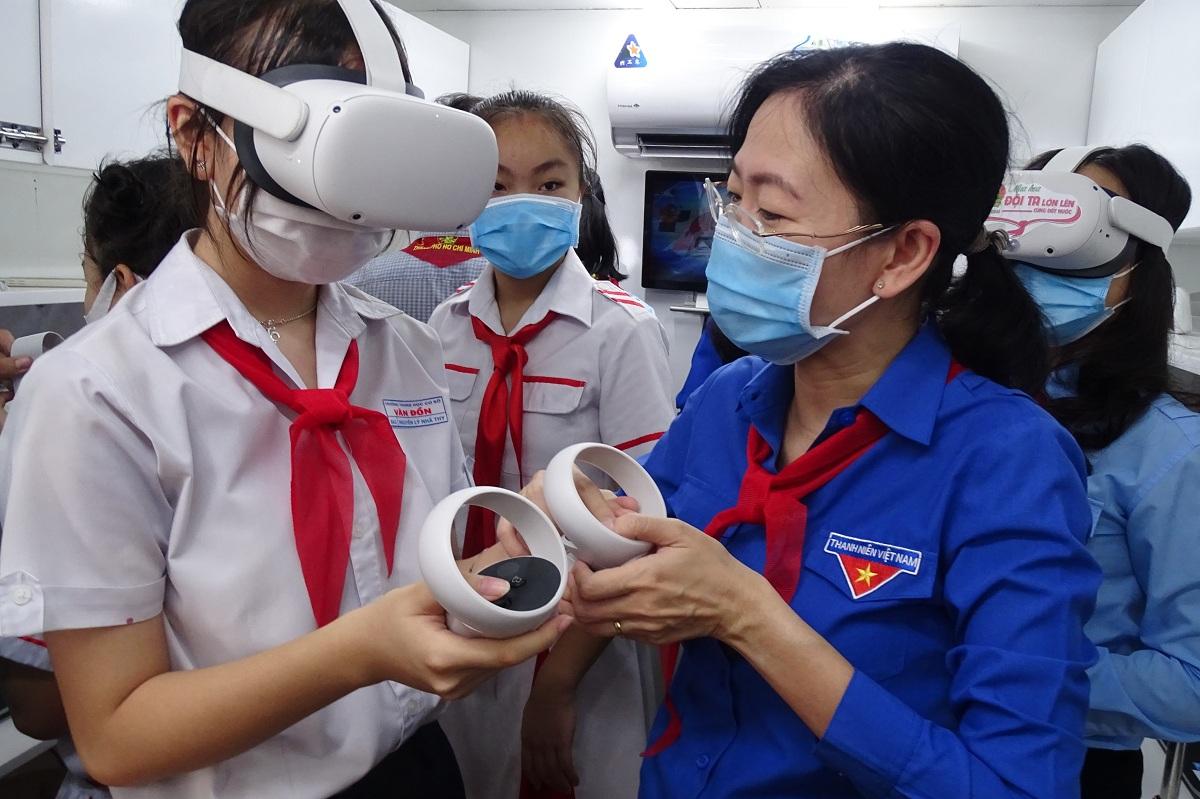 Bà Phan Thị Thanh Phương, Bí thư Thành đoàn TP HCM (trái) hướng dẫn học sinh sử dụng kính thực tế ảo, sáng 15/5. Ảnh: Hà An.