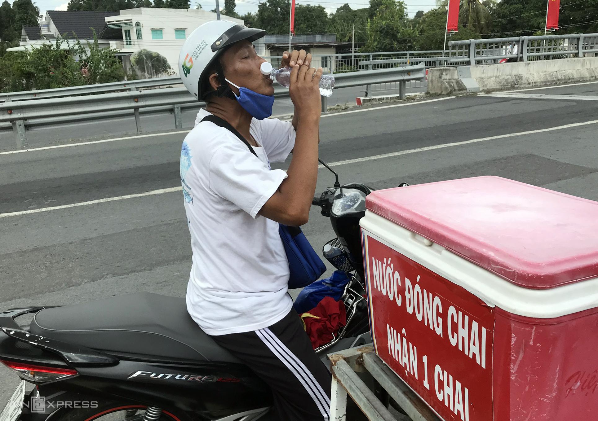 Ngoài cơm, quần áo từ thiện ông Sáng còn để một thùng nước chai miễn phí cho người đi đường uống - Ảnh: Phúc Điền