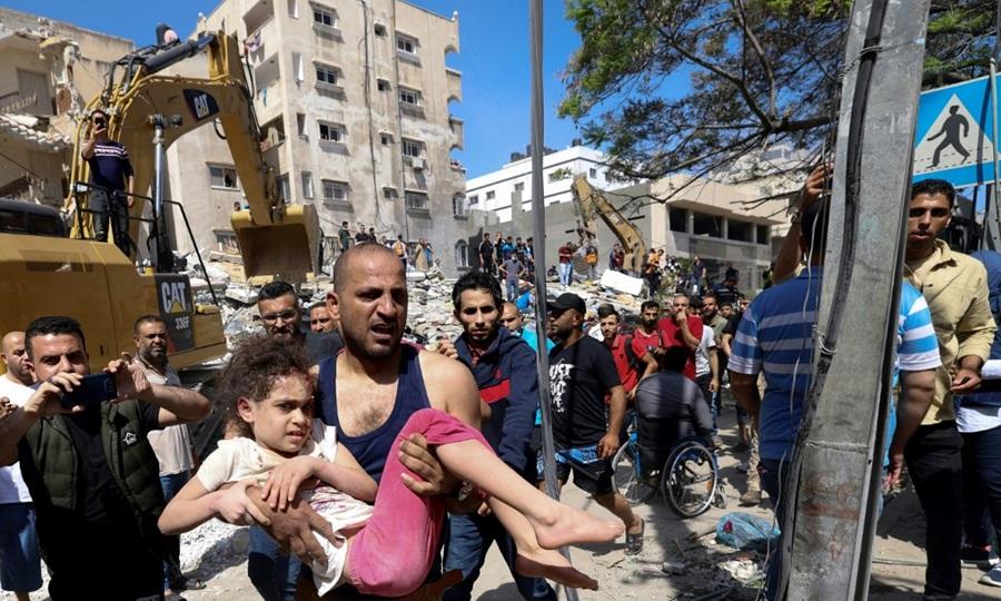 Người Palestine sơ tán một bé gái bị thương khỏi đống đổ nát của tòa nhà bị phá hủy ở khu dân cư Rimal, thành phố Gaza sau đòn không kích của Israel hôm nay. Ảnh: AFP.