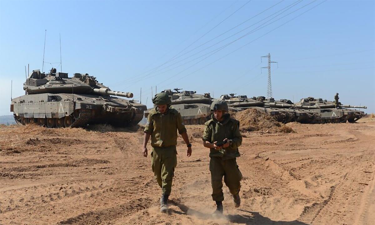 Binh sĩ Israel đứng trước dàn tăng chủ lực Merkava Mk.IV gần đường phân giới với Dải Gaza ngày 16/5. Ảnh: Times of Israel.