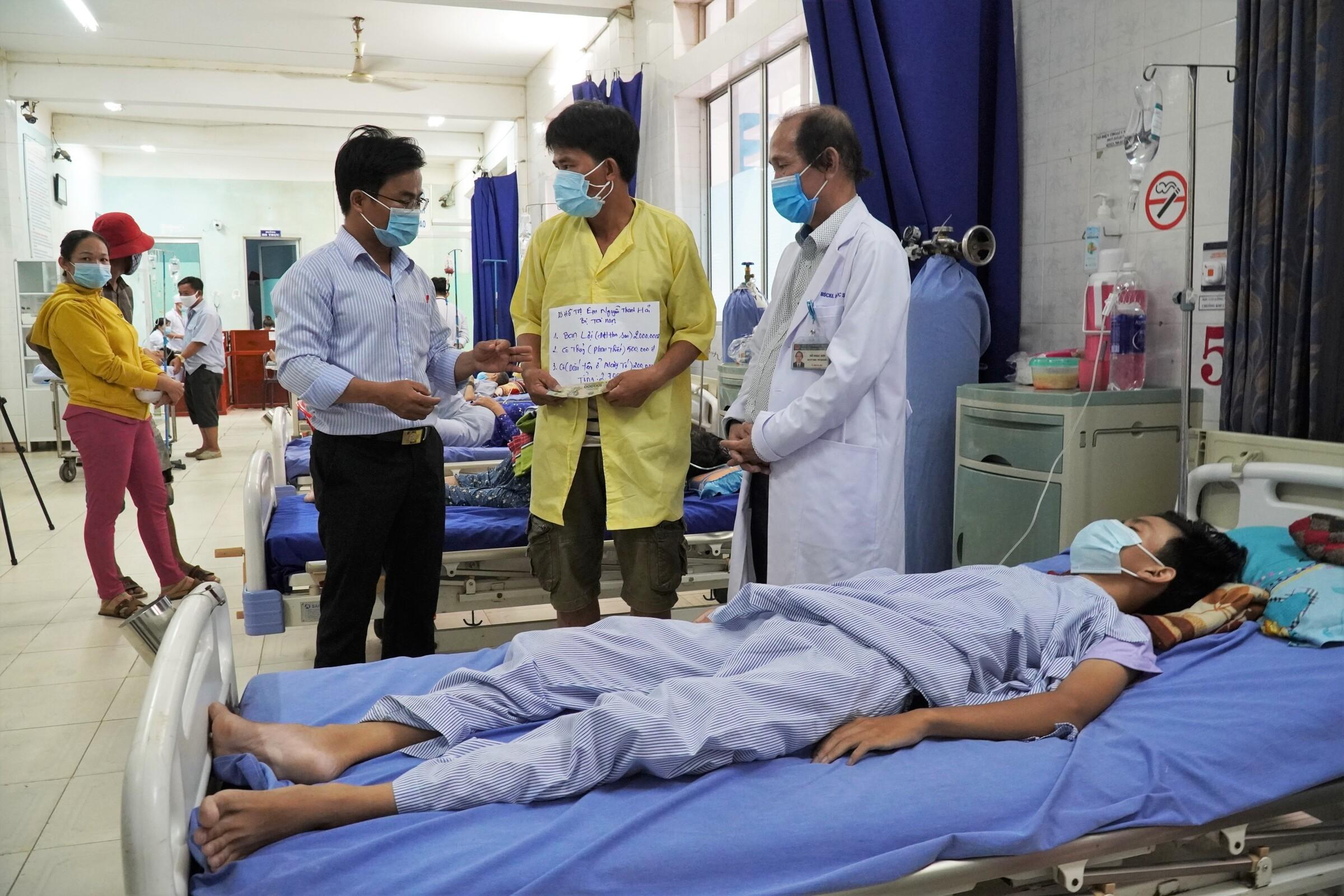 Thầy Võ Văn Cư trao cho ba em Hải tiền hỗ trợ điều trị cho em tại Bệnh viện đa khoa Nam Bình Thuận, ngày 6/5. Ảnh: Việt Quốc.