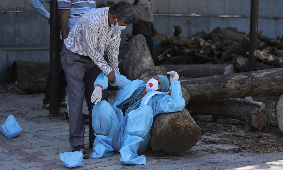 Một người gục ngã vì đau đớn mất người thân do Covid-19 tại khu hỏa táng Jammu hôm 25/4. Ảnh: AP.