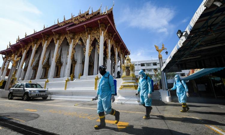 Nhân viên mặc đồ bảo hộ phun khử khuẩn tại khu Klong Toey, Bangkok, Thái Lan, hôm 16/5. Ảnh: Reuters.