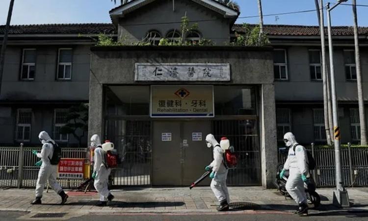 Binh sĩ phun thuốc khử trùng tại một quận ở thành phố Đài Bắc. Ảnh: Reuters.