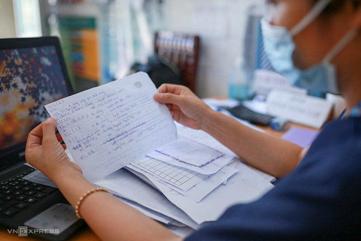 Nhân viên y tế phường Tam Thuận (quận Thanh Khê), kiểm tra lại thông tin người dân đến khai báo y tế. Ảnh: Nguyễn Đông.