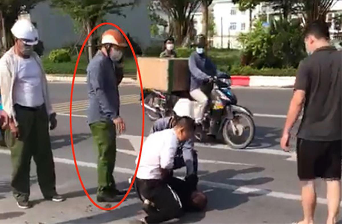Đại uý Lâm (khoanh đỏ) đứng gọi điện thoại khi tài xế Minh khống chế tên cướp. Ảnh: Cắt từ video.