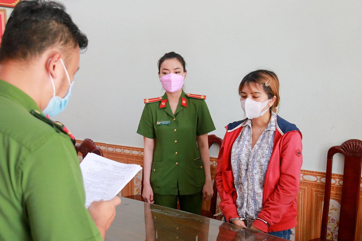 Nghi phạm Lê Thị Kim Khánh (áo khoác đỏ), nghe lệnh bắt tạm giam 4 tháng, trưa 18/5. Ảnh: Nam Vinh.