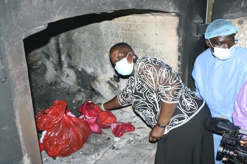 Bộ trưởng Y tế Malawi Khumbize Chaponda đặt túi vaccine vào lò thiêu tại Lilongwe để tiêu hủy ngày 19/5. Ảnh: AP.